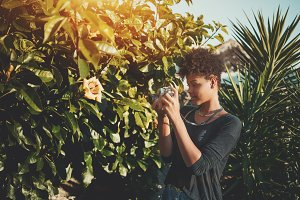 Black girl in garden with film cam