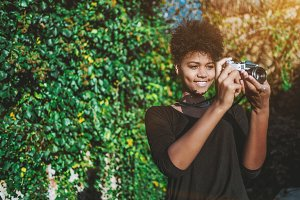 Black girl photographer in a park