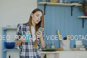 Attractive happy girl dancing and singing in kitchen while using smartphone and listening to music at home in the morning