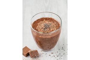 Chocolate chia pudding in glass on gray table