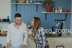 Young joyful couple have fun dancing and singing while having breakfast in the kitchen at home on holidays
