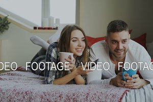 Smiling couple watching TV while lying in bed and drinking coffee at home in the morning