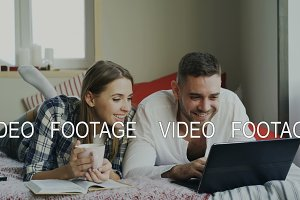 Cheerful man and woman talking and lying in bed reading book and using laptop computer in the morning