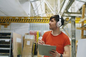 Happy young worker in industrial warehouse listening to music and dancing during work. Man in headphones have fun at workplace.