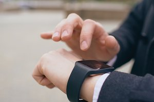 Closeup of businessman hand using his smartwatch touchscreen standing on the street