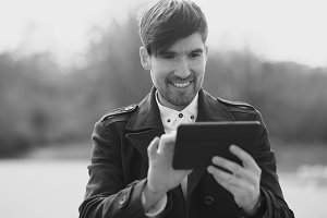 Young smiling businessman using tablet computer during break at the street