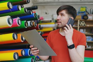 Young worker in warehouse talking smartphone and checking inventory. Man works in sales department of advertising materials