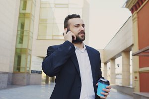 business man talking on cell phone making deals and walking near modern office buildings