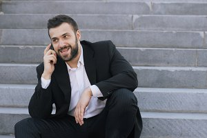 Young bearded business man talking on cell phone making deals sitting on stairs in street
