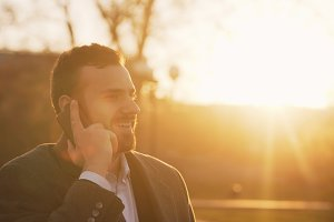 Closeup of Young bearded business man in coat talking at smartphone and making deals on street with sunlight backlit in evening time
