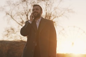 Young bearded business man in coat talking at smartphone and making deals on street with sunlight backlit in evening time