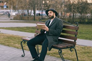 Hipser creative artist man in hat and coat drawing with pen and sketchbook sitting on city street bench at park