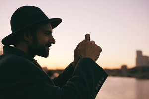 Silhouette of traveler man in hat taking panoramic photo of the city skyline on his smartphone camera at sunset