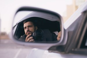 Reflection in side mirror of young private detective man sitting inside car and photographing with dslr camera