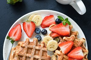 Waffles with berries and cup of tea