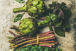 Flat-lay of fresh green and purple vegetables, vertical composition