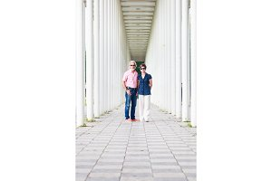 Senior Couple Standing In White Pillar Hallway