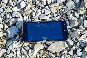 Frustrated phone on the rocks. Glass shattered on rocks on a sma