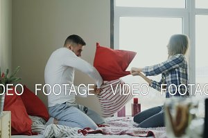 Young happy and loving couple fight pillows in bed at home in the morning