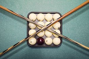 Billiards, billiard table, balls and cue. Balls in the tray and