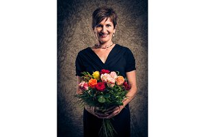 Senior Woman With Bouquet Of Roses, Studio Portrait