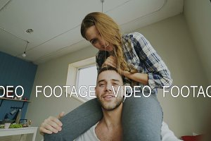 POV shot of cute and loving couple talking online video chat holding smartphone and chatting to friends while girl sitting on man's neck at home