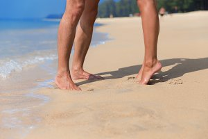 Legs of couple on a beach