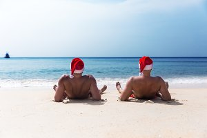two men Christmas hat beach