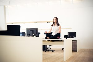 Businesswoman Doing Yoga At The Office