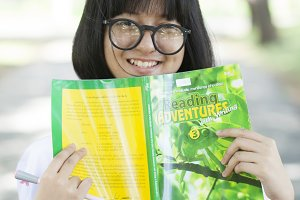 Young woman holding yellow book.
