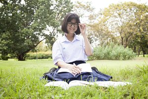 Schoolgirl was reading on the lawn.