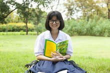 Girl holding a book and smiling.