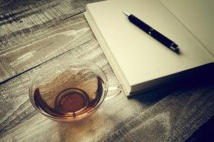 Read tea, blank book and pen