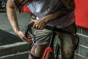 Tattooed biker hipster man in shorts winding the bar tape on a fixed gear bike handlebar