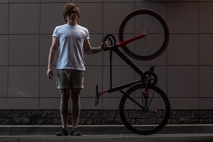 Tattooed biker hipster man in shorts holding a fixed gear bike standing against a grey wall