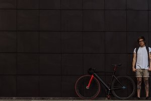 Tattooed biker hipster man in shorts standing against a dark wall next to a fixed gear bike