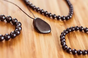 Shungite jewellery lies on a wooden surface