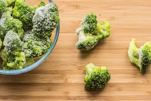 Frosen broccoli in a glass bowl on a wooden surface