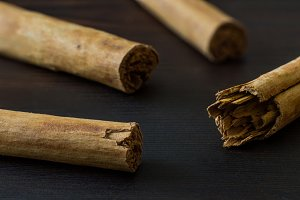 Ceylon cinnamon sticks on black wooden surface close-up
