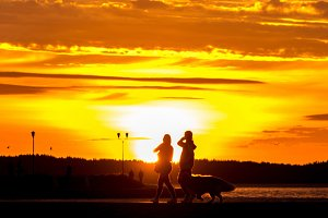 Silhouettes of people on a sunset background on the embankment of Lake Onega. Petrozavodsk. Karelia