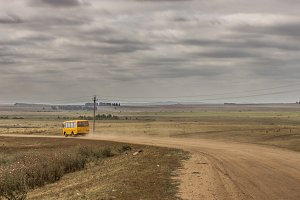 school bus leaves in the distance on a dusty road