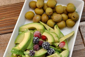 Avocados and olives on white tray