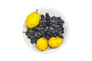 Yellow pear and grapes on the plate