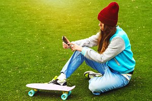 the girl is holding the phone in her hands. active way of life. penny board. sits on the grass