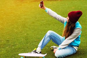 the girl is taking pictures of herself on the phone. sits on the grass. penny board. good weather