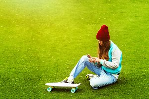 the girl is looking into the phone. sits on the lawn. sport style. penny board is near