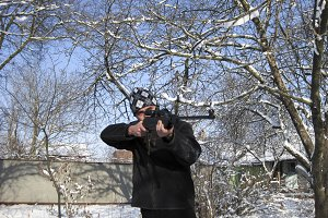 man with an air rifle in a winter park.