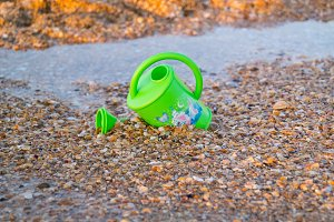 Children toy for watering flowers on the beach