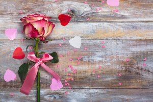 Pink and yellow rose with pink bow and decorative hearts confetti on wooden background