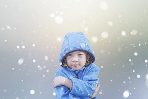 Cool child in blue jacket on snow